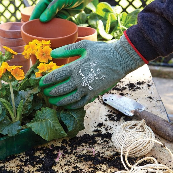 Hands wearing SHOWA 4552 gloves holding a terrecotta pot and yellow flowers