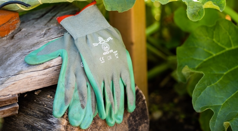 SHOWA 4552 gardening gloves left sat on a piece of wood
