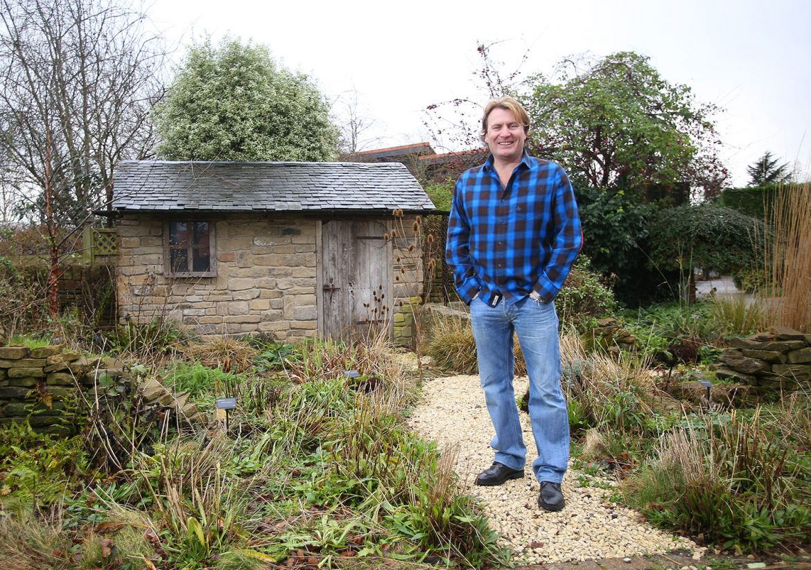 David Domoney wearing a blue/black shirt in a garden with a brick shed in the background