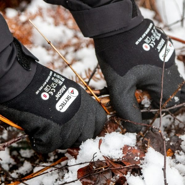 Hands wearing Skytec Argon thermal gloves grabbing twigs from a snowy floor