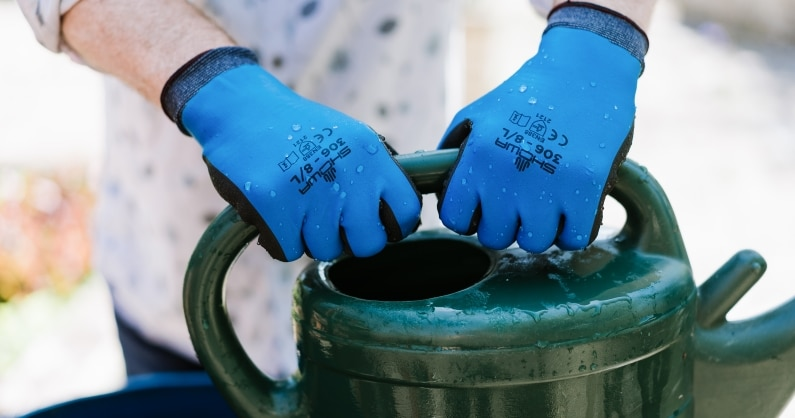 man hands wearing SHOWA 360 gloves holding onto watering can handle with water drops on gloves