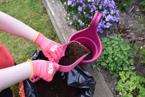 Child's hands wearing pink BUDs gardening gloves putting soil in a pink bucket