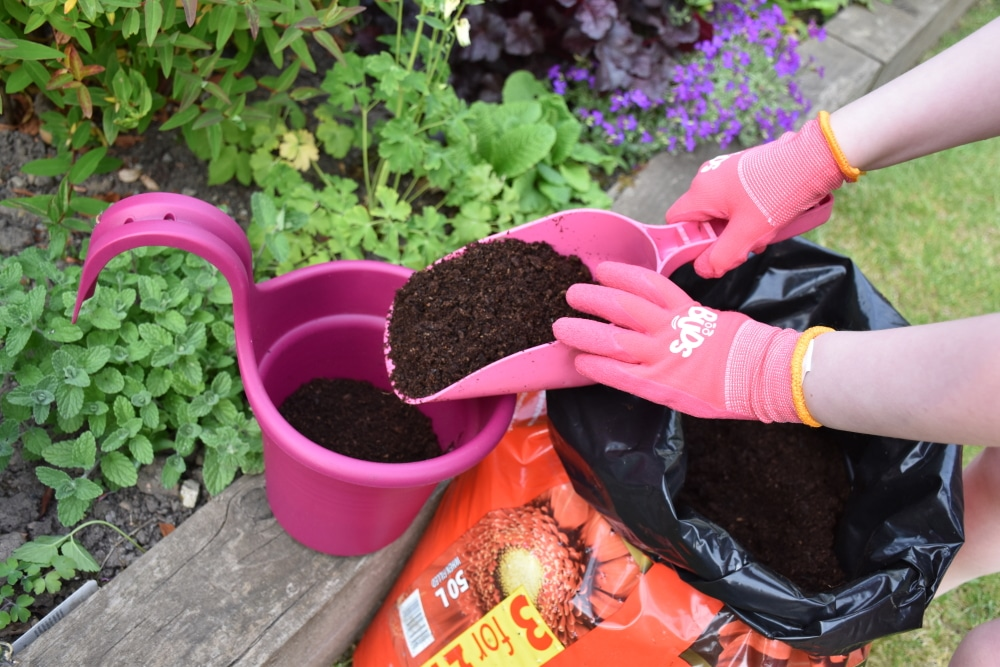 Child hands playing with a bucket, spade and soil wearing pink gardening gloves